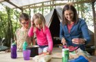 Family cooking outside bell tent